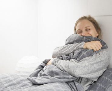 Happy cheerful girl getting enough sleep. Young woman resting in bed, enjoying waking up in good mood. Cozy bedroom concept