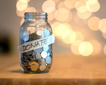 Jar full of coins for donation on wooden desk with blurred background